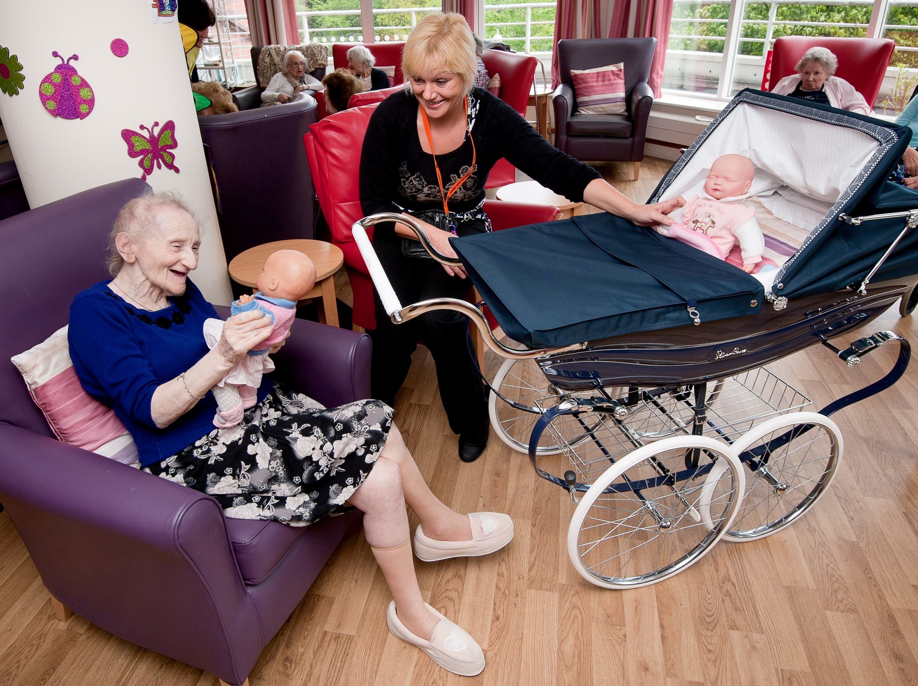 Heathlands Village resident Beatrice Colomberg,79, participating in doll therapy with social care worker Wendy Ward using a Silver Cross pram